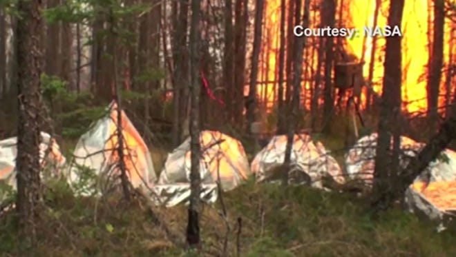 NASA researchers tested more than 200 material combinations before settling on the best for prototype fire shelters, here being tested in Canadian forest fire. More field tests, of the next generatoin of shelter. are expected this summer.