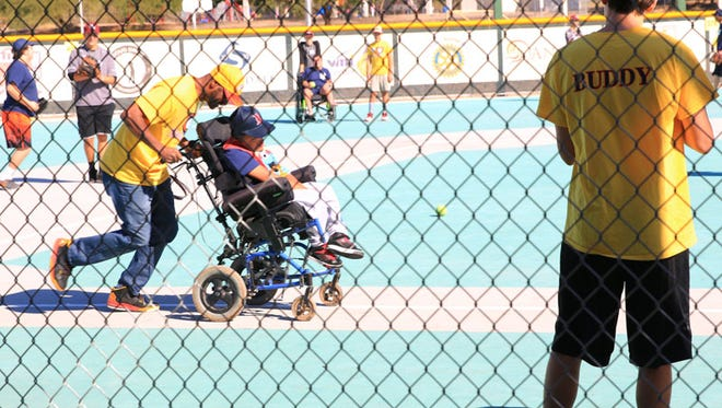 "A baseball ""buddy"" assists a player around the bases at the Miracle League"