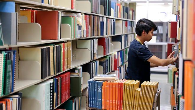 Marvin Vergara Jr. shelves books at Arizona State University's library in Tempe.