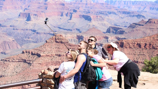 Some environmental groups worry that a National Park Service push to increase visitors – like these tourists at Grand Canyon National Park – in its centennial year will harm parks, but Park Service officials say they are keenly aware of the need to balance conservation and tourism.