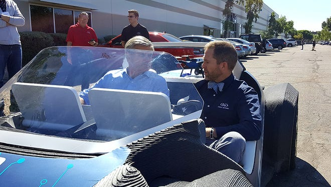 Steve Case (left) and Local Motors CEO John B. Rogers Jr. take a spin in a 3-D printed car.