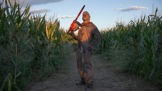 Chicken Lips, a monster that frightens guests at Fear Farm, stands with a chain saw in a corn maze.