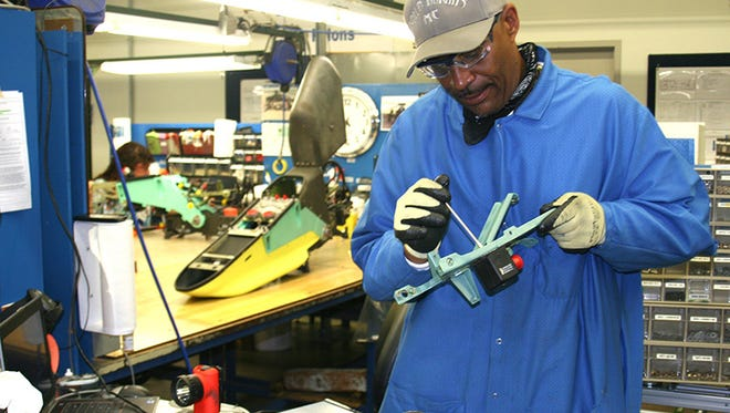 Ronald Young, an employee at Boeing's plant in Mesa, fashions a pylon used to hold weapons on the AH64D attack helicopter.