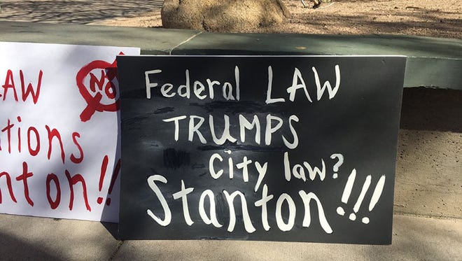 Opponents display signs outside a Phoenix City Council meeting deciding whether Phoenix should declare itself a sanctuary city for immigrants and refugees. (Photo taken by Sarah Jarvis/Cronkite News)
