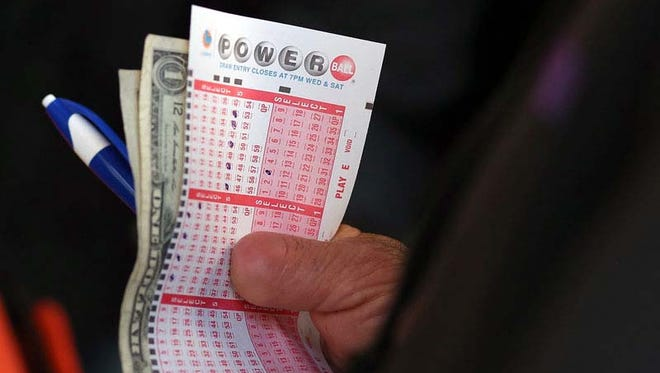 A customer holds a Powerball ticket and money as he waits in line.