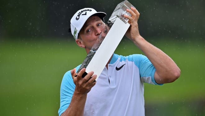 Sweden's Alex Noren kisses the trophy after winning the PGA Championship at Wentworth Golf Club.