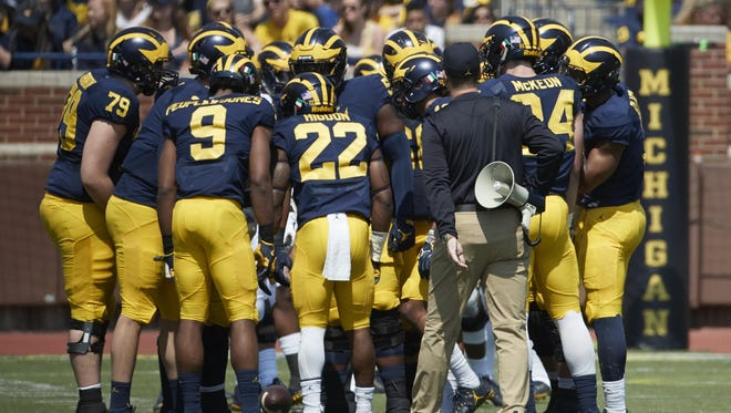 The Wolverines, led by coach Jim Harbaugh, huddle up before a game.