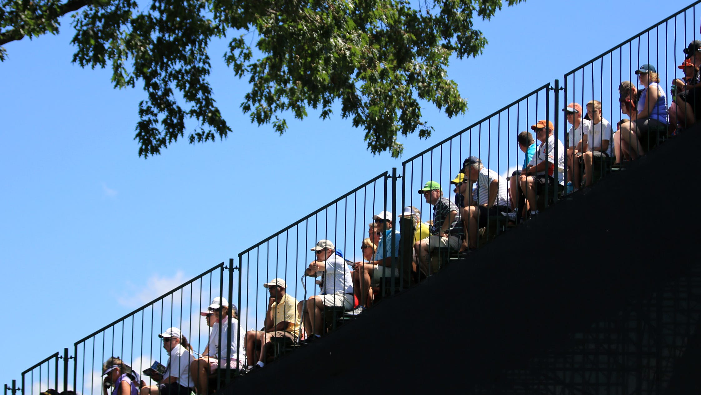 Fans sits in the grandstand on the first hole.