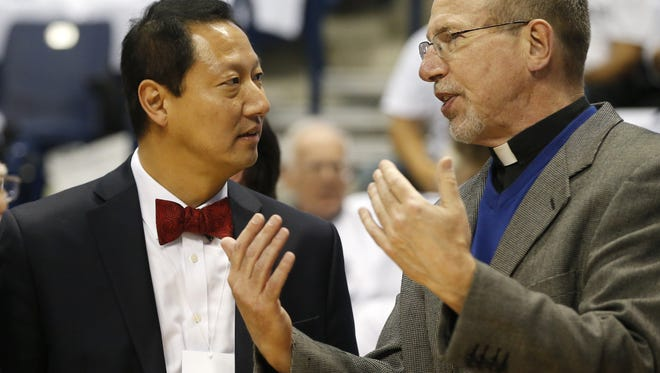 University of Cincinnati president Santa Ono, left, and Xavier University president Michael J. Graham, right, talk before the 83rd annual Crosstown Shootout NCAA basketball game between the Cincinnati Bearcats and the Xavier Musketeers, Saturday, Dec. 12, 2015, Cintas Center in Cincinnati.