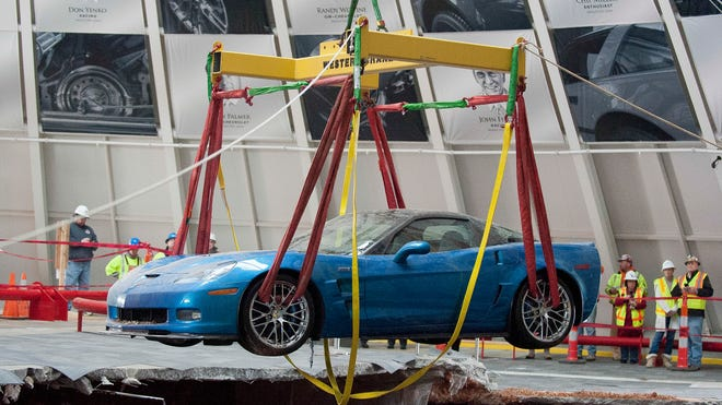 In this March 3, 2014 file photo, one of eight Chevrolet Corvettes is removed from a sinkhole in the Skydome at the National Corvette Museum in Bowling Green, Ky.  Officials at the Corvette Museum voted Saturday to fill in the entire sinkhole that opened up earlier this year and boosted visitors.