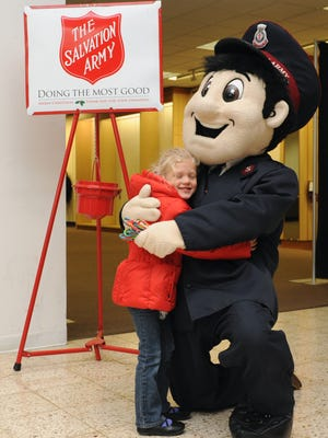 Ally Anna Doyle, 5, of Zanesville, and Dustin Redmond, Salvation Army ministry assistant, dressed as The Salvation Army's Captain Care, share a hug during the organization's first annual Kettle Kickoff event Nov. 15 at the Colony Square Mall in Zanesville.