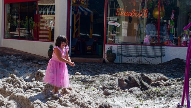 Madison Guessford, 5, plays in the hail outside of the Manitou Springs Penny Arcade, Tuesday July 24, 2018 in Manitou Springs, Colo. People in southern Colorado are cleaning up after heavy rain triggered mudslides and flooding and hail piled up like snow. (Dougal Brownlie/The Gazette via AP)