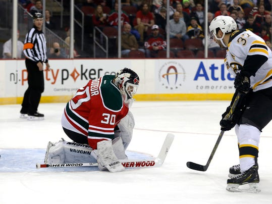 Boston Bruins center Patrice Bergeron, right, scores a goal on New Jersey Devils goalie Martin Brodeur during the first period of an NHL hockey game, Tuesday, March 18, 2014, in Newark, N.J. (AP Photo/Julio Cortez)