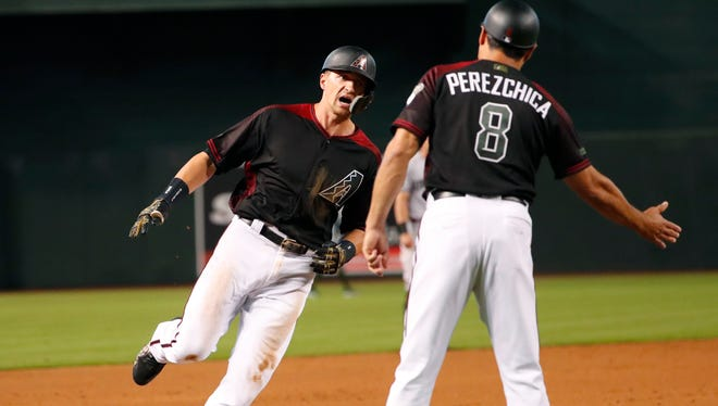 Arizona Diamondbacks shortstop Nick Ahmed is greeted by third base coach Tony Perezchica (8) after hitting a three-run home run against the Cincinnati Reds during the second inning at Chase Field in Phoenix May 28, 2018.