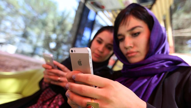 Laleh Osmani, right, the initiator of the online campaign of 'Where is My Name', and an unidentified colleague check their mobile devices at a restaurant in western Herat, Afghanistan, July 20, 2017.