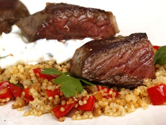 Seared lamb atop red pepper quinoa and tzatziki, prepared by personal chef Marcy Ragan.