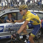 Lance Armstrong, right, and U.S. Postal Service team director Johan Bruyneel, toast with a glass of champagne as they ride towards Paris in the last stage of the 2004 Tour de France.