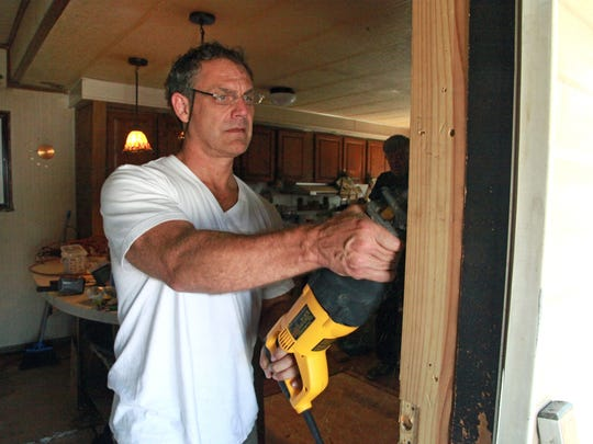 Fletcher Linder repairs the front door frame of Lisa