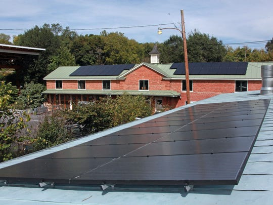 New solar panels on Modern Boy Woodshop in Staunton feed the power grid, generating 95 percent of the cabinet maker's electricity.