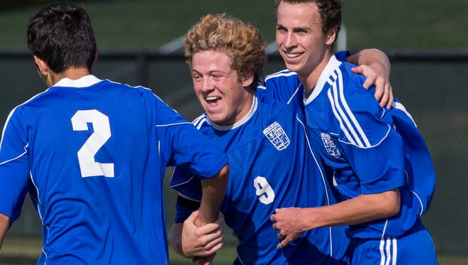 Memorial's Sam Bonano (9) celebrate with his teammates after he scores a goal against Terre Haute North in the first period of the regional game on Saturday afternoon.