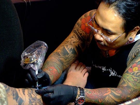 Tattoo artist Dragon Edong Elenzano, of Megavision El Drako Tattoo, working on a client with a tattoo machine.