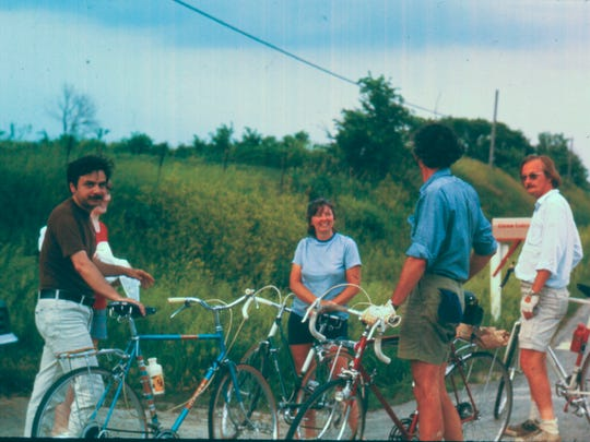 Ann Karras, center, is shown in 1971 along the road with husband John (his back turned), Donald Kaul (far right) and other bicyclists