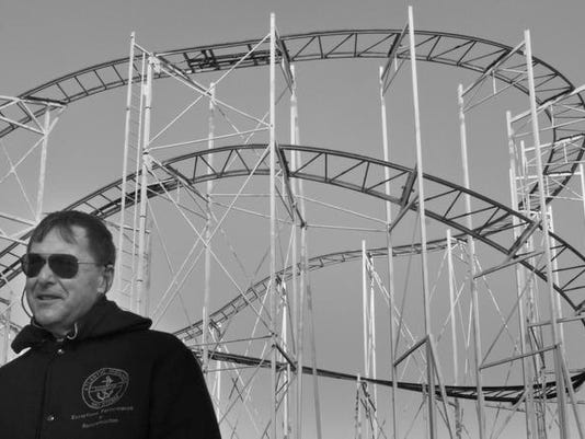 William Gelhaus stands in front of the roller coaster at Keansburg Amusement Park as he details the progress being made
