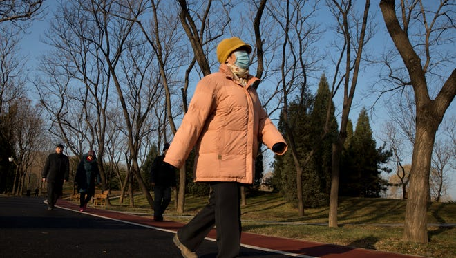 A woman wears a mask at a park as blue sky returns after heavy smog enveloped Beijing on  Thursday.
