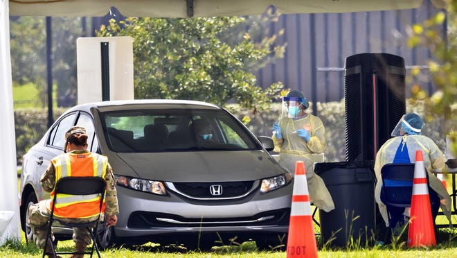 A person is tested for COVID-19 Wednesday at the FITTEAM Ballpark of the Palm Beaches drive-thru facility in West Palm Beach.
