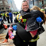 Boston firefighter James Plourde carries Victoria McGrath from the scene after a bombing near the Boston Marathon finish line on April 15, 2013.