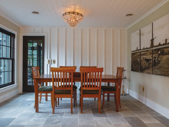 The dining room ceiling is barn board and the floor is slate tiles, giving a sense that this eating area was once a breezeway that had been enclosed at some point.