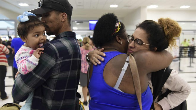 Waritza Alejandro embraces her mother-in-law Maritza Ortiz, before boarding a flight to Tampa with her husband Christian Vega and their daughter Tiana, in Carolina, Puerto Rico, Wednesday, Nov. 8, 2017. The couple lost their home to Hurricane Maria. The disaster wrought by Maria has set off an anguished debate across Puerto Rico, where friends, family and co-workers are arguing fiercely over the morality of leaving the blacked-out island vs. staying to fulfill a patriotic duty to rebuild. (AP Photo/Carlos Giusti)