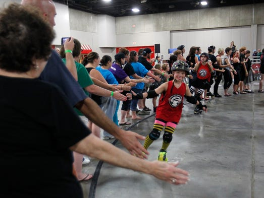 Fan cheer and high five skaters before the start of the games the game at the Fairground West Hall in Louisville, Kentucky.       July 25, 2014