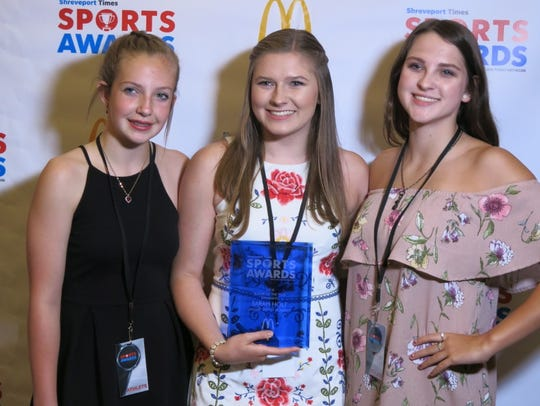 Sarah Holt, Calvary Baptist Academy (middle), took home Player of the Year Award for Girls Swimming and poses with two friends for a photo op.