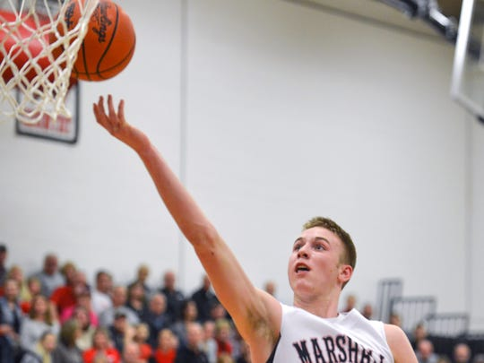Marshall's Jeremy Luciani (22) goes for a layup during Friday night's matchup against rival Harper Creek.