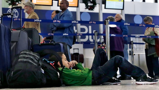Seven-year-old Jordan Knowles rests his head against his family's luggage. They were rebooking their JetBlue flight back home to the Bahamas at Boston's Logan Airport on Monday, when JetBlue halted operations in Boston, New York and New Jersey due to severe weather.