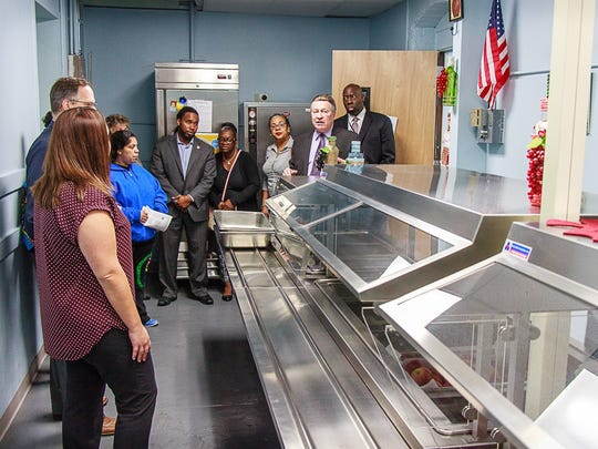 District officials tour the improved cafeteria.
