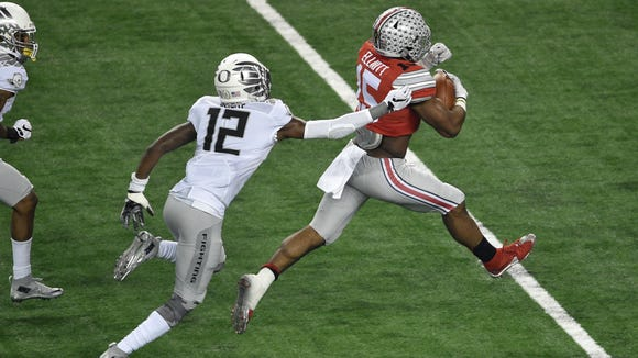 Jan 12, 2015; Arlington, TX, USA; Ohio State Buckeyes running back Ezekiel Elliott (15) eludes Oregon Ducks defensive back Chris Seisay (12) during the game at AT&T Stadium. The Buckeyes defeated the Ducks 42-20. Mandatory Credit: Jerome Miron-USA TODAY Sports