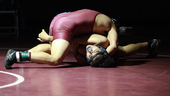 Richard Rico of the Blackhawks, top, defeats John Razo during the Indio at La Quinta wrestling meet, January 12, 2017.
