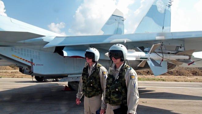 Russian pilots stand outside their Su-30 jet fighter, armed with air-to-air missiles, before a take off on Oct. 5, 2015 at Hmeimim airbase in Syria.
