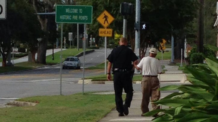 JSO officer helps legally blind man across the street.