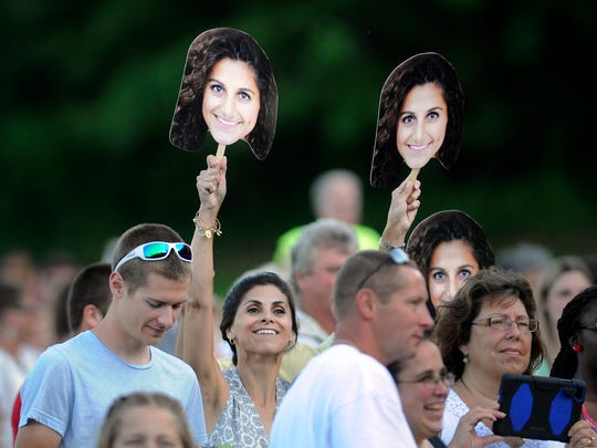 Kim Vona waves photographs of her daughter, Reina Vona, a candidate for graduation at Highland High School, at commencement ceremonies on Thursday in the Town of Lloyd.
