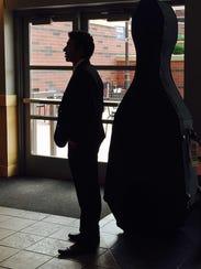 Edgar Martinez stands next to his instrument inside