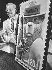 This Aug. 13, 1984 file photo shows Ray Bell, the man who cared for Smokey Bear after the young cub was rescued from a forest fire 50 years ago, is shown with an oversized copy of the Smokey Bear stamp.