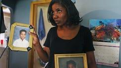 Lisa Ettienne, of Milwaukee, displays two photos of
