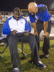 Ida Baker coach Dwayne Mack, left, looks at stats on an iPad, compiled by Jaron Gonzalez, before second-half play at the Ida Baker vs Riverdale football game in 2015.