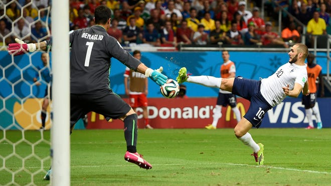 France's Karim Benzema (right) shoots to score the team's fourth goal past Switzerland goalkeeper Diego Benaglio during their World Cup Group E match Friday at the Fonte Nova arena in Salvador.