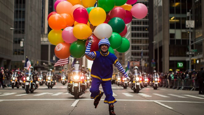 A performer carries balloons across Sixth Avenue during the Macy's Thanksgiving Day Parade, in New York on Nov. 24.