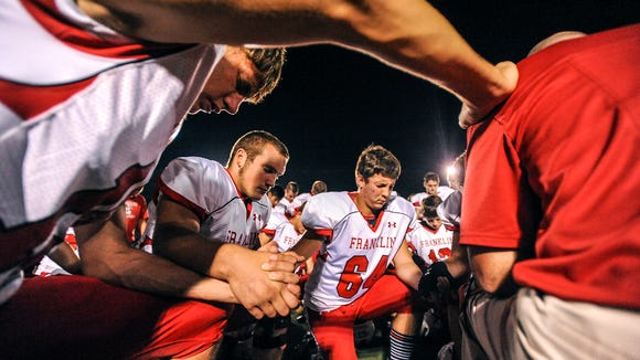 The Franklin football team joins hands in prayer after Friday's 31-15 win at Enka.