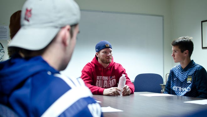 Dale Earnhardt Jr., center, talks to students at Essex High School on Thursday. The NASCAR driver visited the school as part of an agreement with his sponsor, the National Guard, to speak with students around the country.